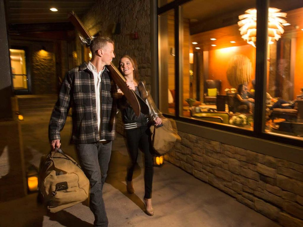 Couple with luggage outside Teton Mountain Lodge